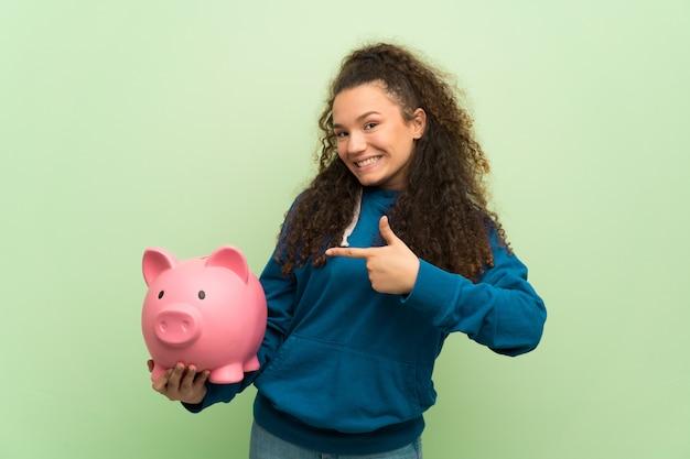 Ragazza dell'adolescente sopra la parete verde che tiene un porcellino salvadanaio Foto Premium