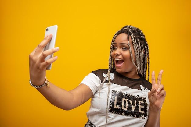 Ragazza dell'afroamericano che prende le foto del selfie con il suo telefono cellulare su giallo Foto Premium