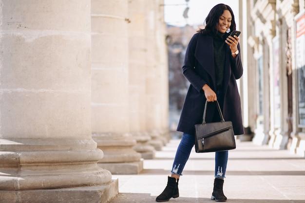 Ragazza dell'allievo dell'afroamericano con il telefono dall'università Foto Gratuite