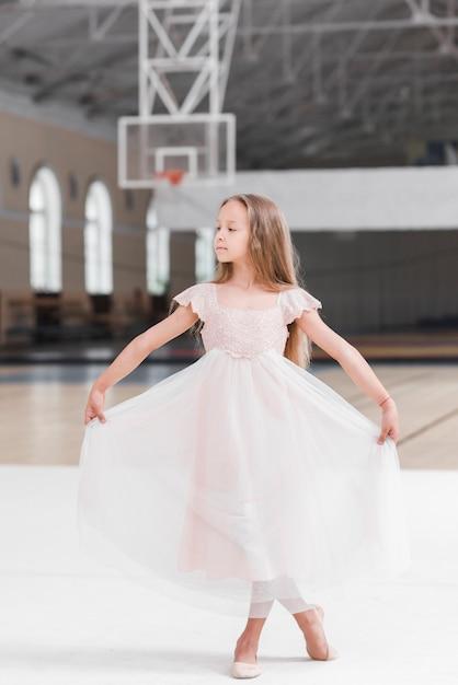 Ragazza della ballerina che poising nella classe di ballo Foto Gratuite