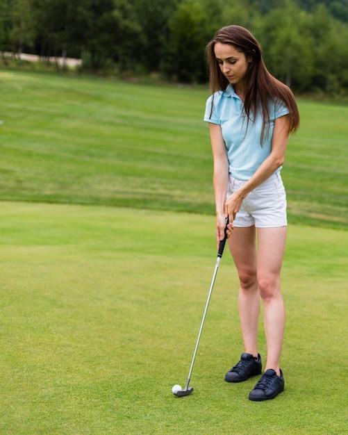 Ragazza della foto a figura intera che colpisce la palla da golf Foto Gratuite