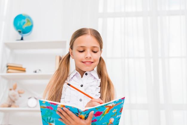 Ragazza della scuola elementare in piedi facendo i compiti Foto Gratuite