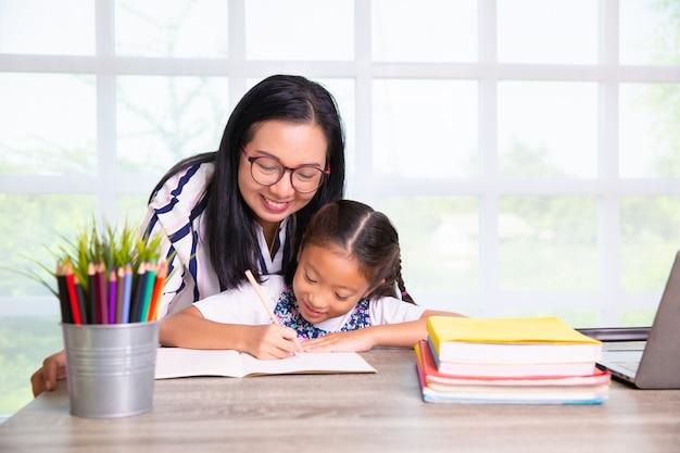 Ragazza della scuola primaria che studia con l'insegnante nella classe Foto Premium