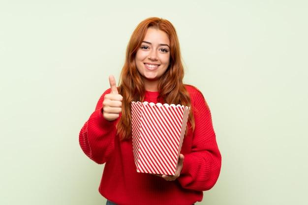 Ragazza della testarossa dell'adolescente con il maglione sopra verde isolato che tiene una ciotola di popcorn Foto Premium