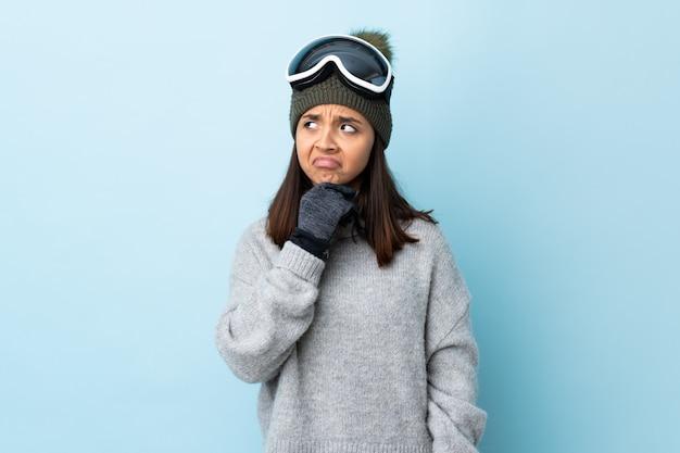 Ragazza dello sciatore della corsa mista con i vetri di snowboard sopra la parete blu che ha dubbi Foto Premium