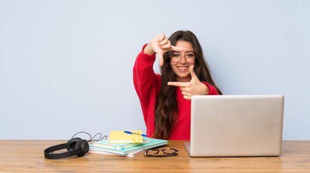 Ragazza dello studente dell'adolescente che studia in un fronte di messa a fuoco della tavola. simbolo di inquadratura Foto Premium