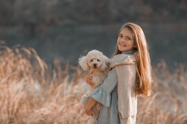 Ragazza di 12 anni cammina un animale domestico per strada Foto Premium