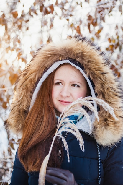 Ragazza di aspetto europeo in una passeggiata nella foresta invernale, parco, inverno e neve, salute, abiti invernali, giacca Foto Premium