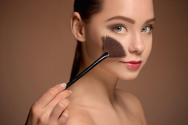 Ragazza di bellezza con pennello trucco. pelle perfetta applicare il trucco Foto Gratuite