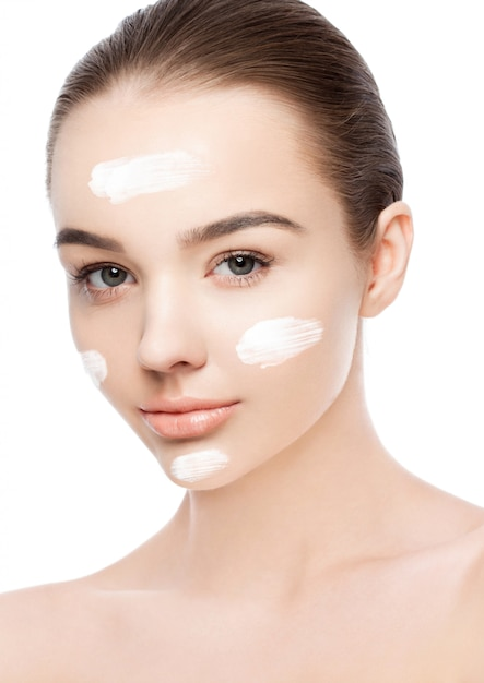 Ragazza di bellezza con trucco naturale crema viso Foto Premium