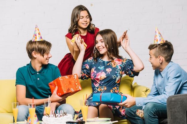 Ragazza di buon compleanno guardando i suoi amici tenendo scatole regalo Foto Gratuite