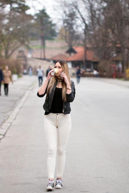 Ragazza di città con smart phone e tazza di caffè Foto Premium