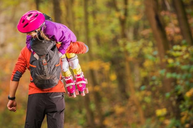 Ragazza di pattinaggio del rullo con il padre scaricare