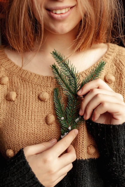 Ragazza di smiley del primo piano con il ramoscello dell'albero di abete Foto Gratuite