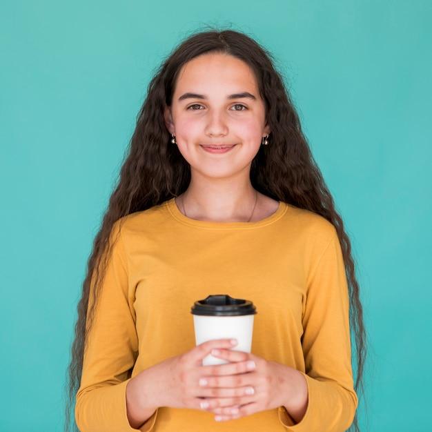 Ragazza di smiley di vista frontale che tiene la sua bevanda Foto Gratuite