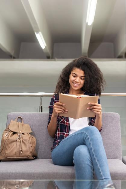 Ragazza di smiley sulla lettura dello strato Foto Gratuite