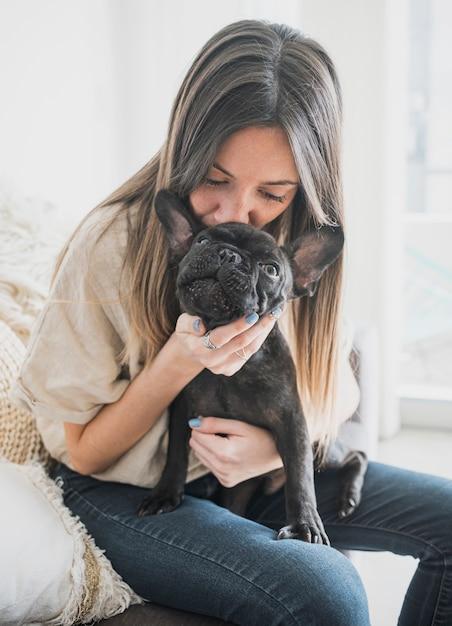 Ragazza di vista frontale che bacia il suo cagnolino Foto Gratuite