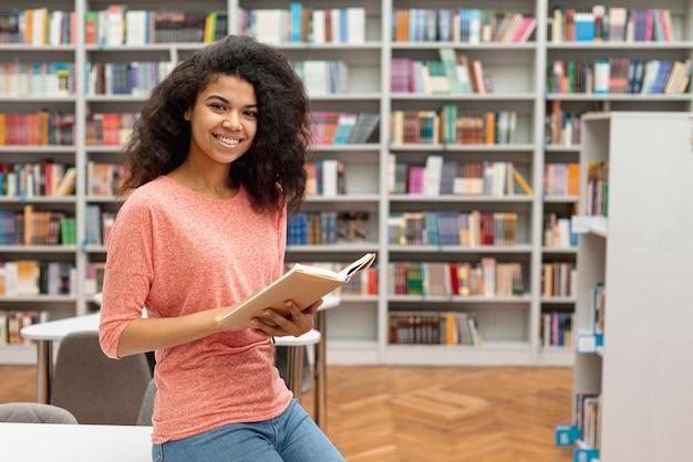Ragazza di vista laterale alla lettura delle biblioteche Foto Gratuite
