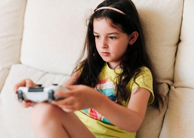 Ragazza di vista laterale che gioca i video giochi con il regolatore Foto Gratuite
