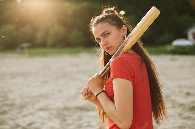 Ragazza di vista laterale con la mazza da baseball Foto Gratuite