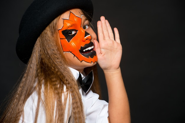 Ragazza divertente del bambino in costume della zucca per halloween. trucco di halloween. arte faccia. Foto Premium
