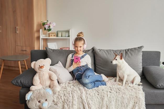 Ragazza e cane posa sul divano in cuffia, ascoltando musica con il suo smarthphone Foto Premium