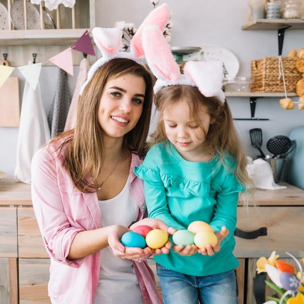 Ragazza e madre nelle orecchie del coniglietto che tengono le uova di pasqua in mano Foto Gratuite