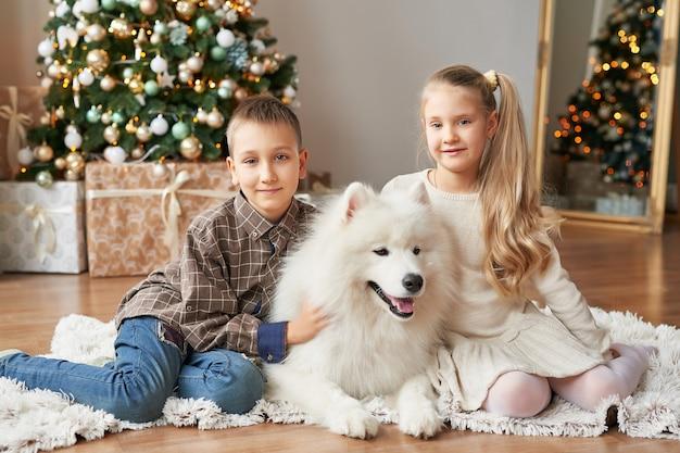 Ragazza e ragazzo con cane samoiedo a natale Foto Premium