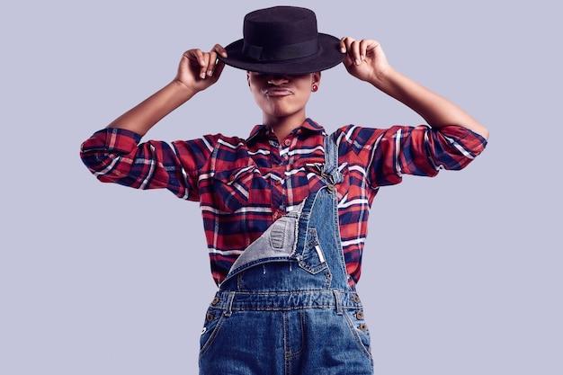 Ragazza elegante hipster nera con i capelli corti in una camicia a quadri e tuta di jeans. Foto Premium