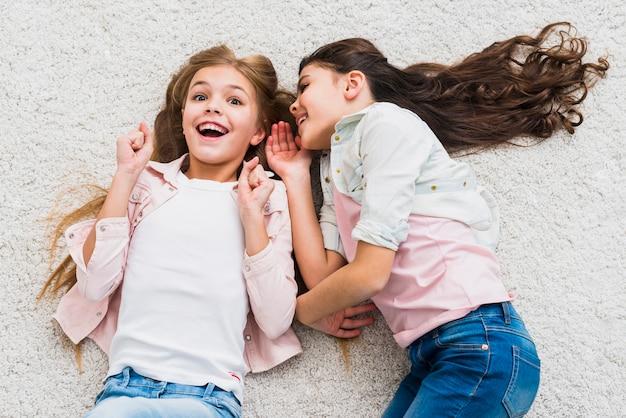 Ragazza emozionante che ascolta amico che bisbiglia all'orecchio che si trova sul tappeto Foto Gratuite