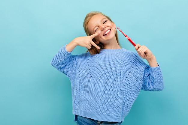 Ragazza europea attraente che tiene uno spazzolino da denti in sue mani sulla parete blu-chiaro Foto Premium