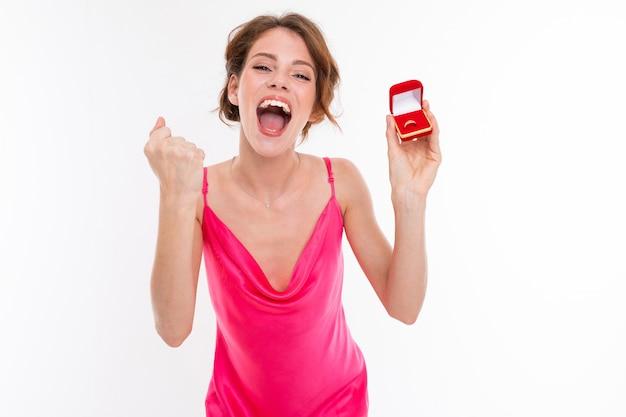 Ragazza felice affascinante in un vestito rosa con una scatola con una fede nuziale su un fondo bianco Foto Premium