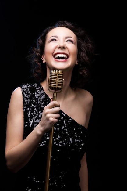 Ragazza felice bella ragazza che rideva azienda retrò microfono Foto Gratuite