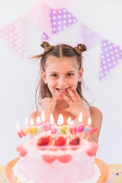 Ragazza felice che mette le sue dita in bocca in piedi dietro la torta di compleanno Foto Gratuite