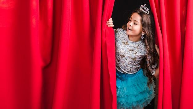 Ragazza felice che osserva attraverso la tenda rossa in scena Foto Gratuite
