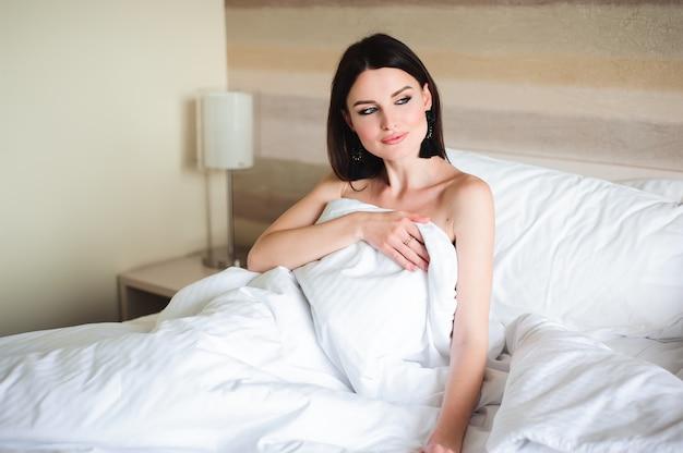 Ragazza felice che sveglia allungando armi sul letto di mattina. Foto Premium