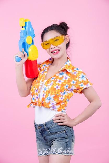 Ragazza felice che tiene una pistola a acqua rosa del fondo. Foto Gratuite