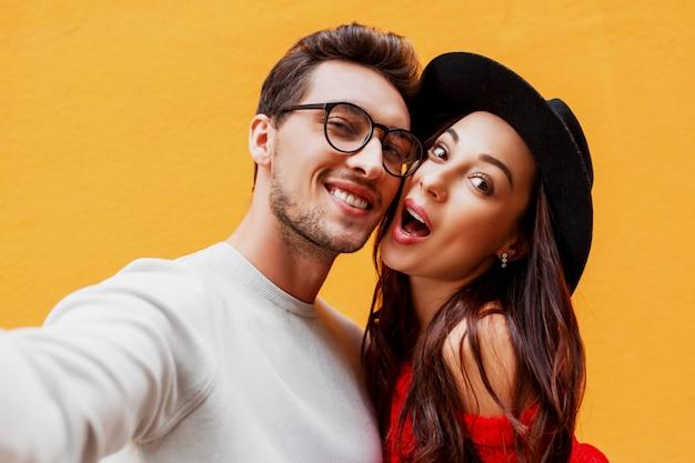 Ragazza felice con il suo ragazzo che fa autoritratto dal telefono cellulare. muro giallo. indossa un maglione lavorato a maglia rosso. atmosfera da festa di capodanno. Foto Gratuite