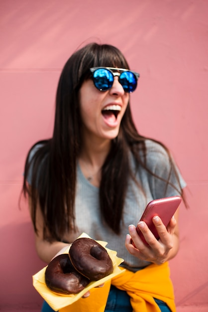 Ragazza felice del colpo medio con le ciambelle e lo smartphone Foto Gratuite