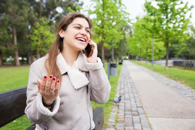 Ragazza felice dell'allievo eccitata con la conversazione divertente del telefono Foto Gratuite