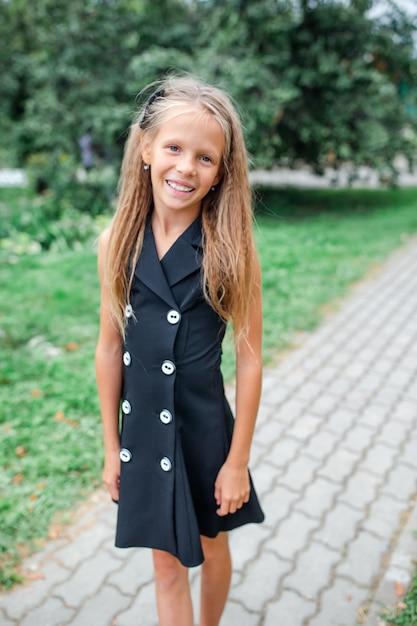 Ragazza felice della scuola che posa nei ourdoors della scuola Foto Premium