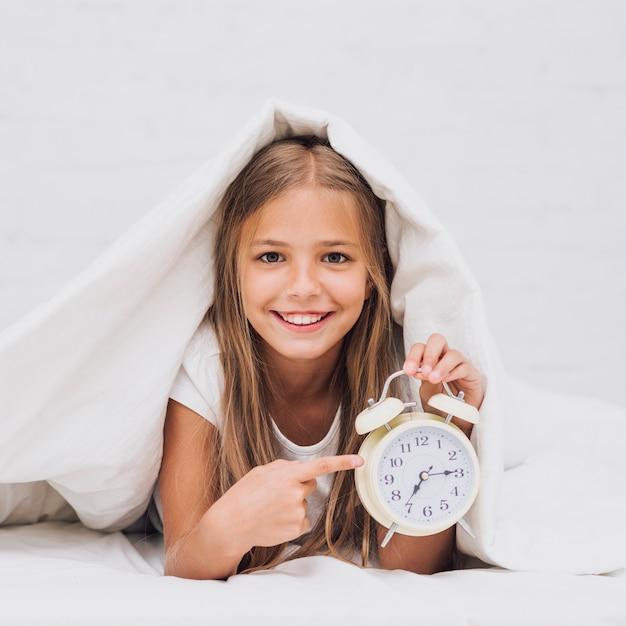 Ragazza felice di vista frontale che indica all'orologio Foto Gratuite