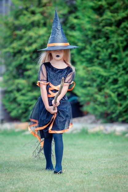 Ragazza felice in costume di halloween con jack zucca. dolcetto o scherzetto Foto Premium
