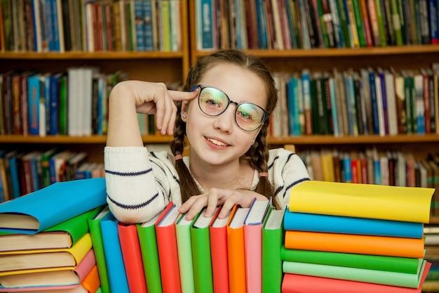 Ragazza felice in vetri con i libri nella libreria Foto Premium