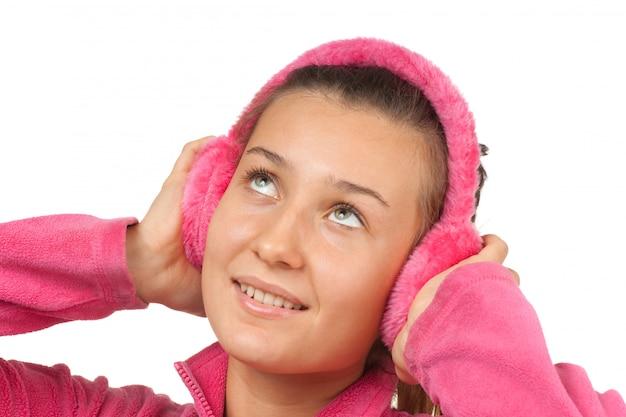 Ragazza felice teenager in cuffie rosa isolate su bianco Foto Premium