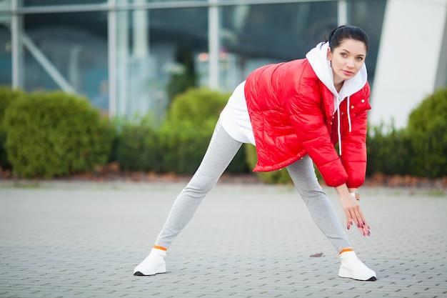 Ragazza fitness. giovane donna sportiva che si estende nella città moderna. stile di vita sano nella grande città Foto Premium