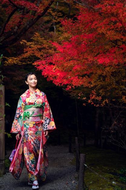 Ragazza giapponese in abito tradizionale kimono a piedi nel vecchio tempio di kyoto Foto Premium