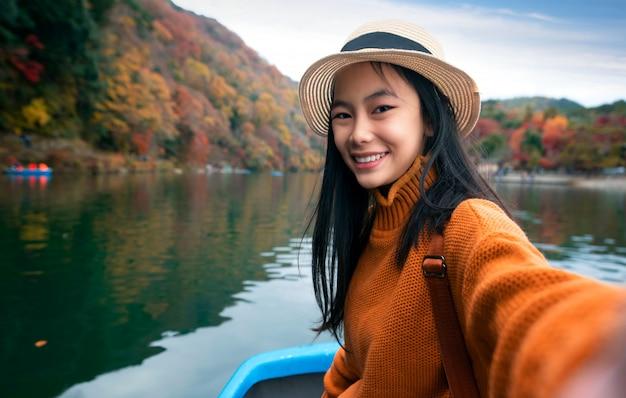 Ragazza giapponese sulla barca in arashiyam Foto Premium