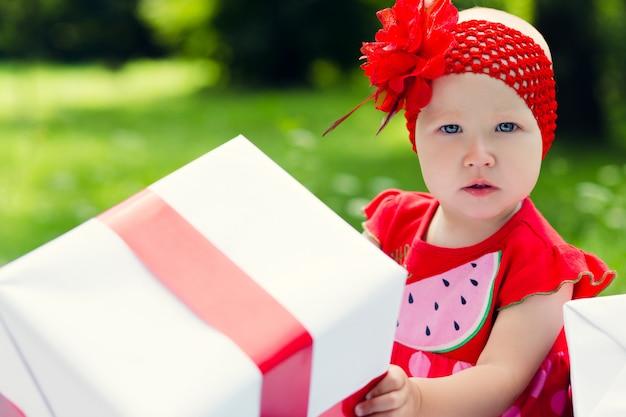 Ragazza gioiosa bambino con scatole regalo colorate Foto Premium