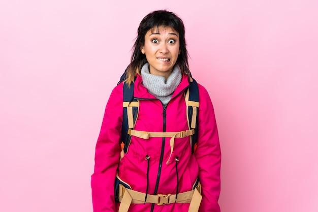 Ragazza giovane alpinista con un grande zaino sul muro rosa con dubbi e con espressione faccia confusa Foto Premium